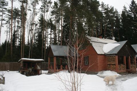 Кирпичный дом и бревенчатая баня в окружении леса